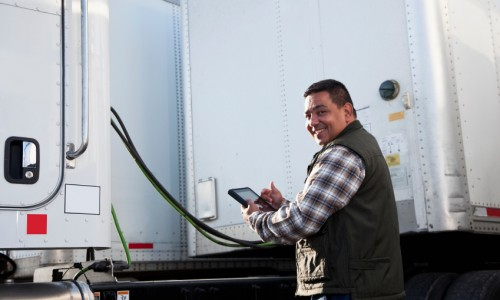 Hispanic truck driver with digital tablet